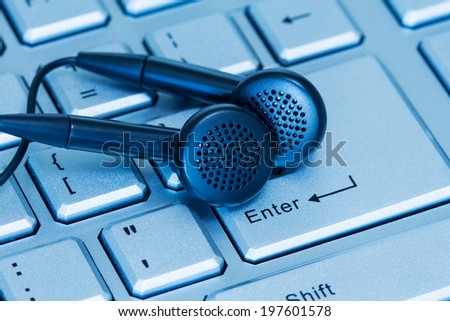 Headphones and computer keyboard, concept of digital music  - stock photo
