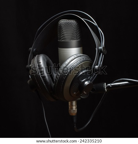 Headphones and condenser microphone isolated on the dark background - stock photo