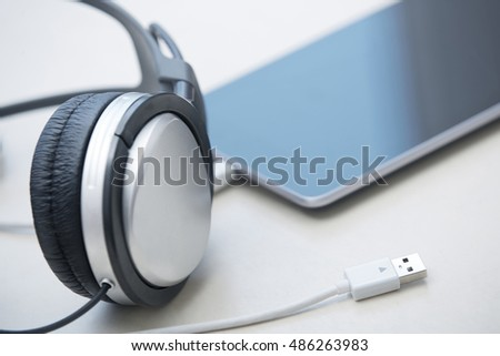 Headphones and digital tablet on a table