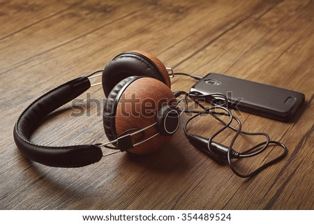 Headphones and smartphone on brown wooden background