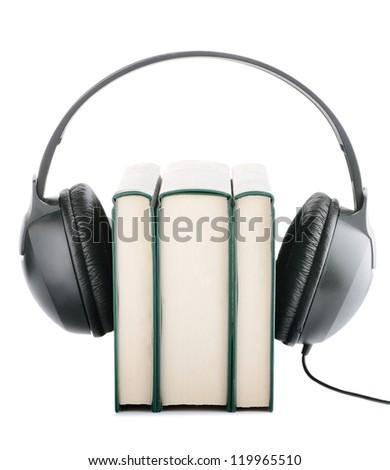 Headphones around books suggesting listening to books instead of reading them - stock photo