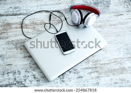 Headphones connected to a smartphone and a Laptop computer.  - stock photo