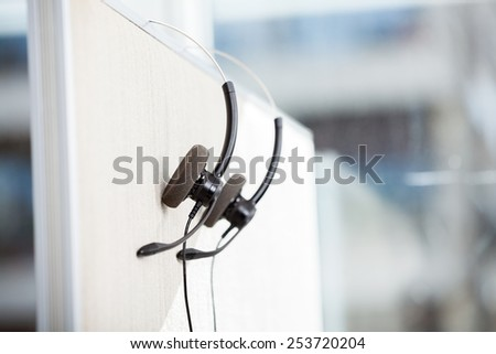 Headphones hanging on cubicle partition in empty office - stock photo