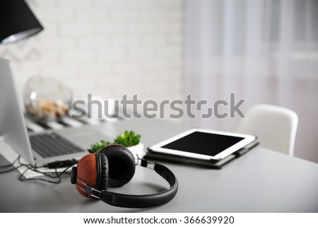 Headphones, laptop and the tablet on gray table against defocused background - stock photo