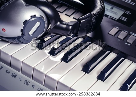 Headphones lying on top of a synthesizer - stock photo