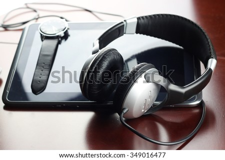Headphones on a table next to the tablet and a clock