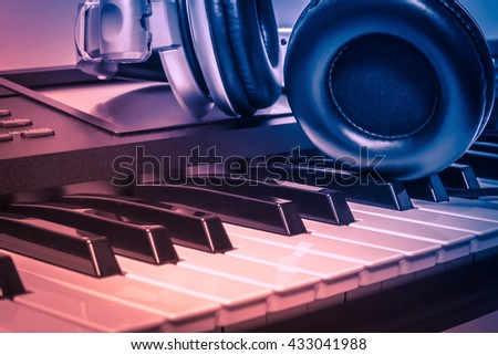 headphones on electric piano background by the  music instruments background. - stock photo