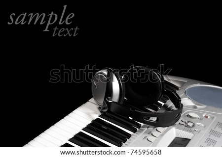 Headphones on keyboard, isolated in black