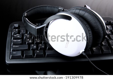 Headphones on keyboard isolated on black - stock photo