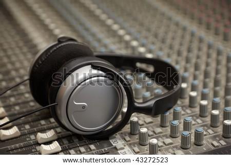 headphones on old dirty sound mixer panel - stock photo