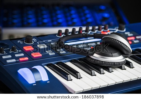 Headphones on top of a synthesizer inside a recording studio - stock photo