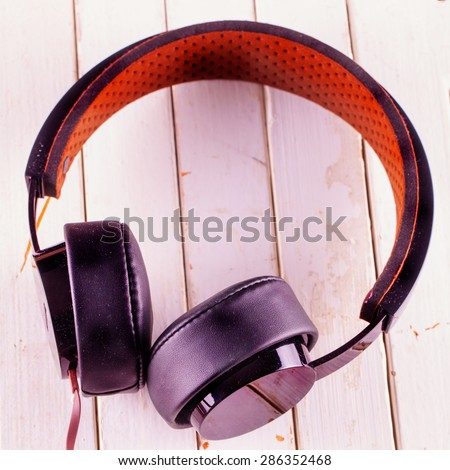 Headphones over white wooden background, square image - stock photo