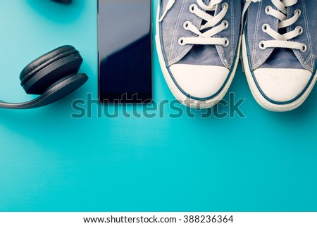 headphones, smart phone and sneakers on colorful background - stock photo