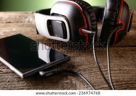 Headphones with mobile phone on wooden desk - stock photo