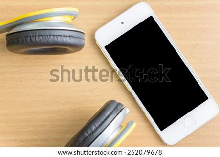 headphones with mobile smartphone on desk - stock photo