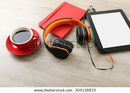 Headphones with tablet and cup of coffee on wooden table close up - stock photo