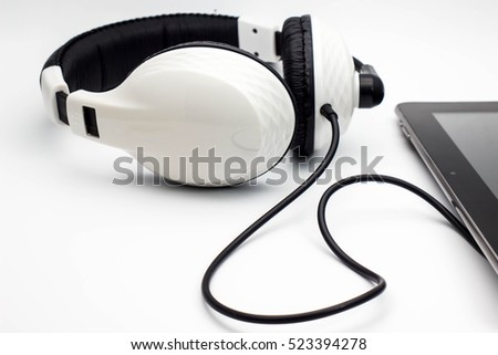 Headphones with tablet on white background.