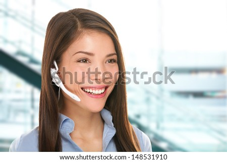 Headset customer service woman secretary at call center talking friendly smiling happy in office. Beautiful young mixed race Caucasian / Asian Chinese business woman working at hotline. - stock photo
