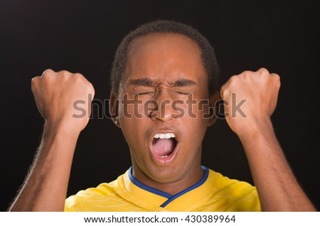 Headshot dark skinned male wearing yellow football shirt in front of black background, eyes closed and mouth open cheering with arms raised