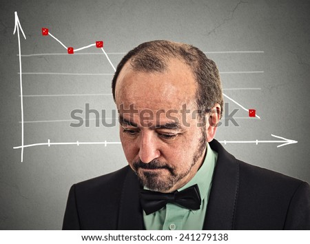 Headshot depressed stressed business man looking down financial market chart graphic going down on grey office wall background. Poor economy crisis meltdown loss concept. Face expression emotion - stock photo