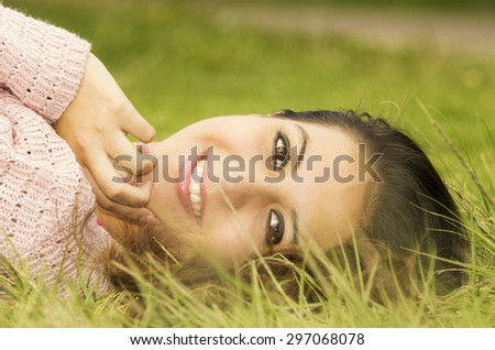 Headshot hispanic female brunette model with head resting on grass and looking sideways towards camera smiling. - stock photo