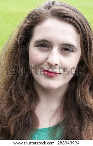 Headshot of a beautiful olive skinned young female student who has unique hazel eyes, and thick curly/wavy hair. - stock photo