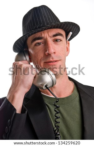 Headshot of a Caucasian Male Wearing a Fedora Style Hat and Talking on the Phone - Head and Shoulders - stock photo