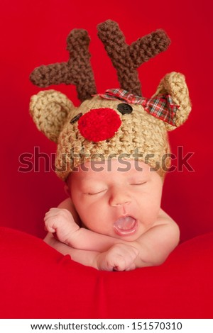 Headshot of a one week old newborn baby wearing a crocheted reindeer hat. Shot in the studio on a red blanket. - stock photo