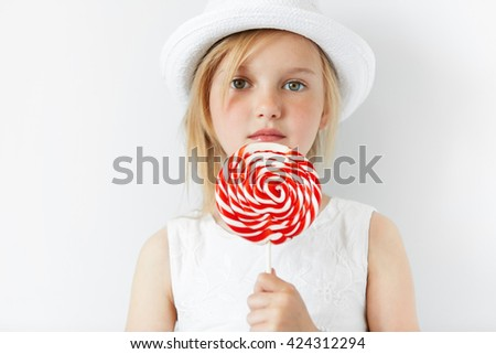 Headshot of adorable 5-year old female child licking spiral candy looking and smiling at the camera. Cute little girl with fair hair and green eyes holding big lollipop. Happy childhood concept  - stock photo