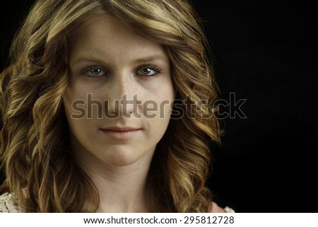 Headshot of an attractive youang lady against a black background - stock photo