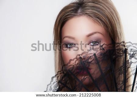 headshot of beautiful female model holding a fan - stock photo