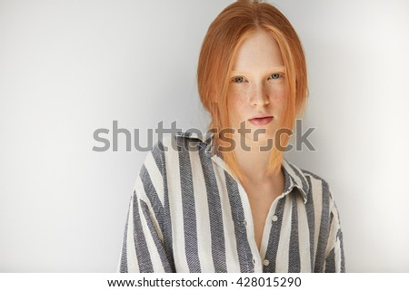 Headshot of cute Caucasian redhead freckled teenager model in striped night suit, looking at the camera with serious and thoughtful expression, ready for going to bed. Youth and skin care concept.  - stock photo