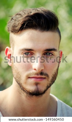 Headshot of handsome young man outdoors, serious expression - stock photo