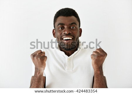 Headshot of happy successful African American student or businessman looking with winning expression, fists pumped, celebrating success against white wall background. Life perception, achievement - stock photo