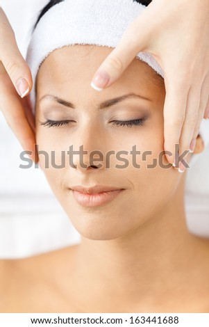 Headshot of naked woman with closed eyes getting face massage. Concept of relax and medicine - stock photo