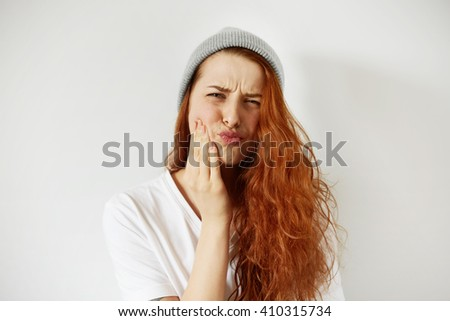 Headshot of redhead teenage woman pressing her cheek with painful expression as if she is having terrible toothache. Negative human emotions, face expressions, body language. Selective focus  - stock photo