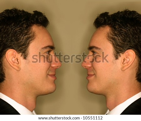 Headshot of young businessman looking at copy of himself