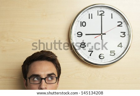Headshot of young businessman wearing spectacles looking at clock on wooden wall in office - stock photo