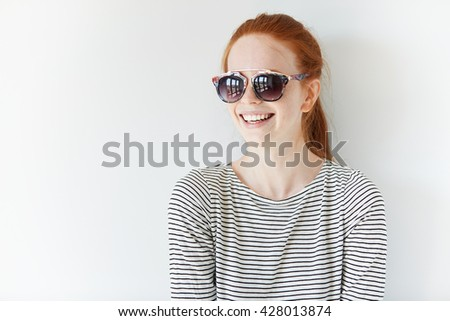 Headshot of young Caucasian redhead female office worker or student relaxing and having fun with her friends indoor. Hipster teenager wearing stylish striped top looking away with happy expression - stock photo