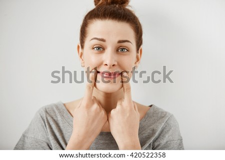 Headshot of young Caucasian woman making fake smile with her fingers stretching the corners of her mouth. Portrait of student girl trying to stay positive after failing final exams at university   - stock photo