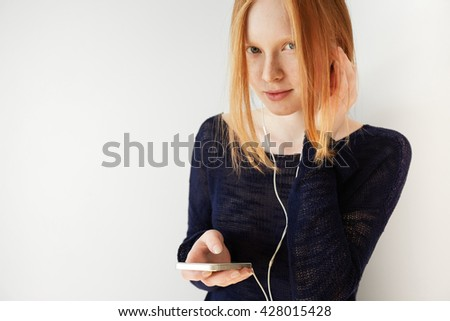 Headshot of young girl listening, enjoying music on her mobile mp3 player wearing white earphones posing against white studio wall background with copy space for your text or advertising content  - stock photo