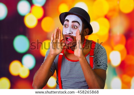 Headshot pantomime man with facial paint posing for camera using hands around mouth yelling, blurry lights background - stock photo