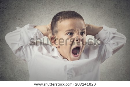 Headshot, Portrait Angry Child Screaming, hands on head isolated grey wall background. Negative Human face Expressions, Emotions, Reaction, life Perception. Conflict, confrontation concept. Behavior