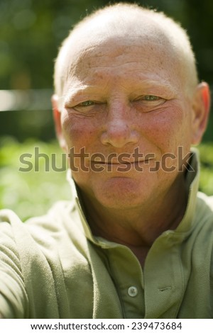 headshot portrait happy smiling middle age senior handsome man in casual polo shirt shallow depth of field