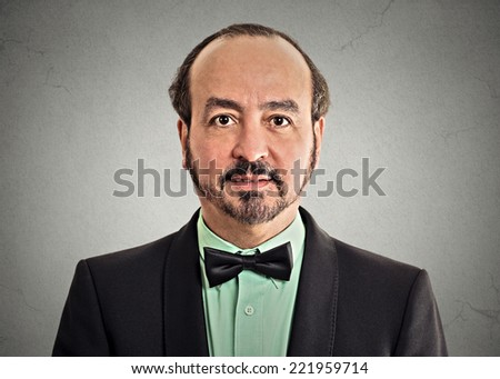 headshot portrait mature gentleman handsome man in elegant black suit wearing bow tie isolated on grey wall background. Positive face expression handsome man in elegant black suit - stock photo