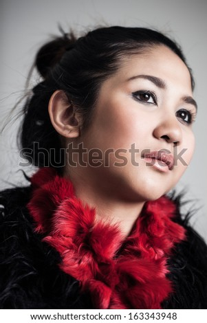 Headshot portrait of a beautiful young Asian woman with serious expression wearing red scarf - stock photo