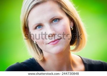 Headshot portrait of an early 30s casual  beautiful blond woman at the park on a sunny summer day - stock photo