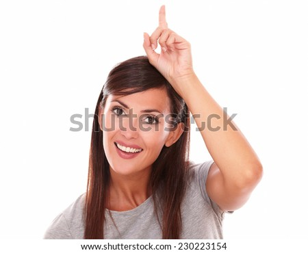 Headshot portrait of attactive woman pointing up while smiling and looking at camera on isolated white background - copyspace - stock photo