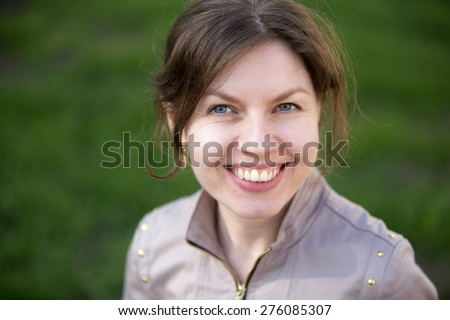 Headshot portrait of happy smiling woman in park