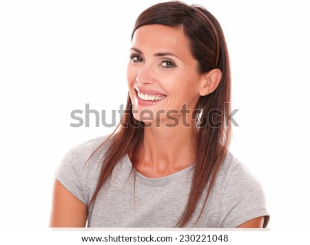 Headshot portrait of smiling happy latin woman looking at camera on isolated studio - copyspace - stock photo